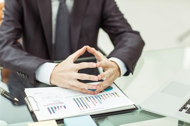Бизнесмен размышляет о финансовой политике компании, сидя за столом в офисе