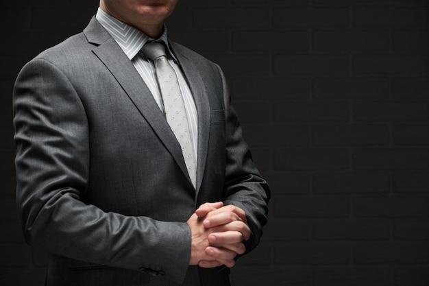 Businessman portrait dressed in gray suit, dark wall background
