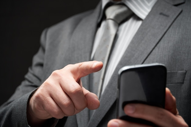 Businessman portrait dressed in gray suit, dialing by smartphone, dark wall background