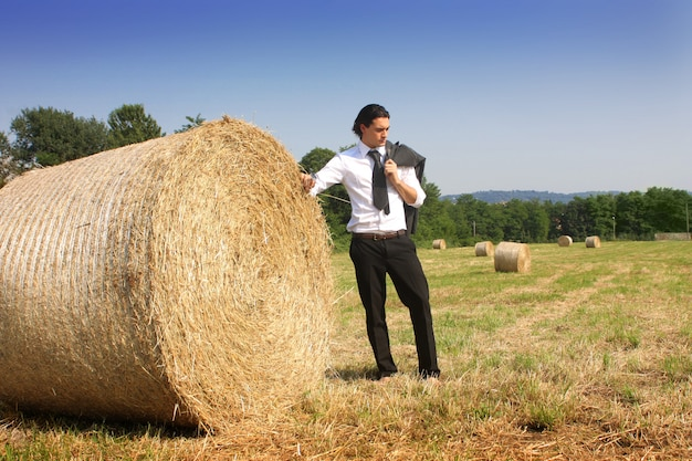 Businessman posing at a bale