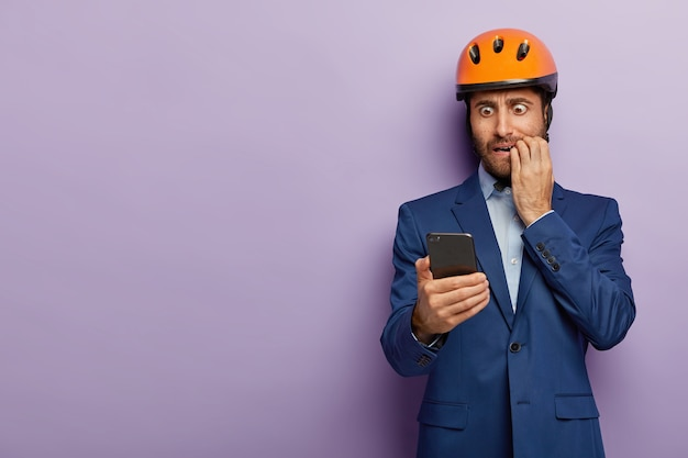 Businessman posing in classy suit and red helmet at the office