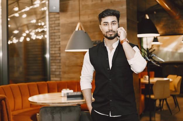 Бизнесмен позирует в кафе