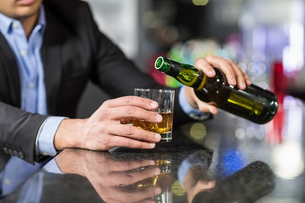 Businessman pouring whisky in glass