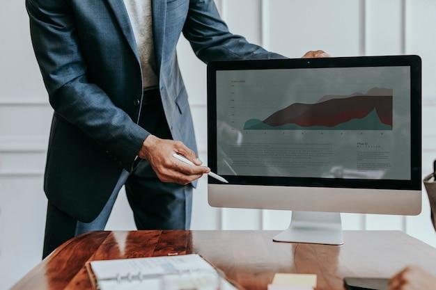 コンピューターのデスクトップ上でプロジェクトを提示するビジネスマン