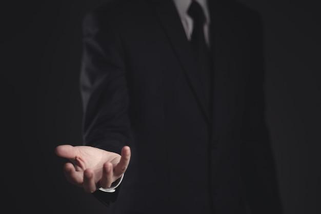 Businessman presenting in black suit on black