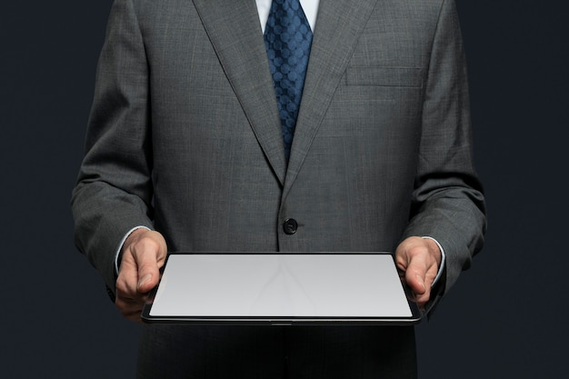 タブレットの高度な技術から投影する目に見えないホログラムを提示するビジネスマン