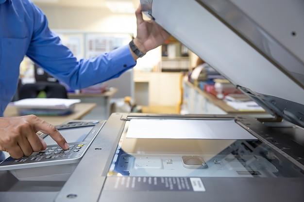 ビジネスマンはコピー機のパネルのボタンを押します。