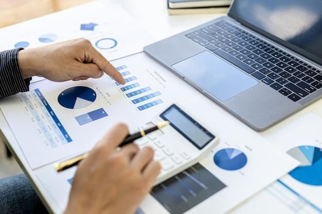 Бизнесмен нажимает на калькулятор для расчета цифр на финансовых документах, он проверяет точность финансовых отчетов, чтобы принести на встречу со своим партнером. концепция финансового менеджмента