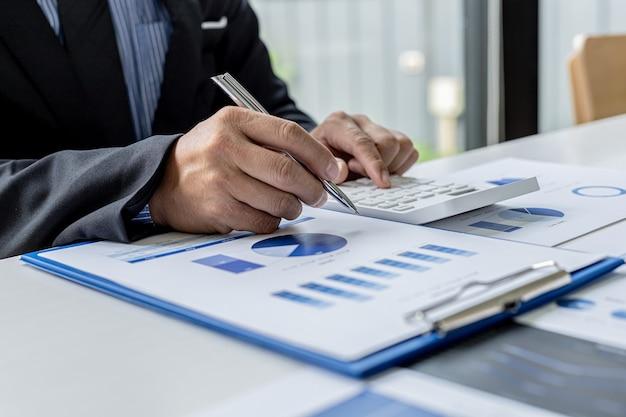 Бизнесмен нажимает белый калькулятор, он владелец компании, он проверяет финансовые документы компании в своем офисе, финансовые документы показывают формат диаграммы. концепция финансового менеджмента