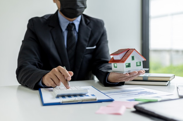 Businessman presses a calculator to calculate the amount on a housing estate sales document, he is meeting with the sales manager to place a sale and make promotions, marketing plans to increase sales
