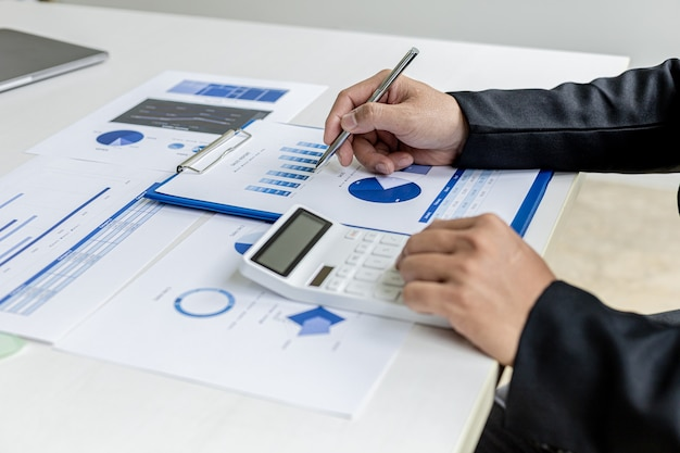 Businessman presses a white calculator, he is the owner of the company, he is checking company financial documents in his office, financial documents show chart format. concept of financial management
