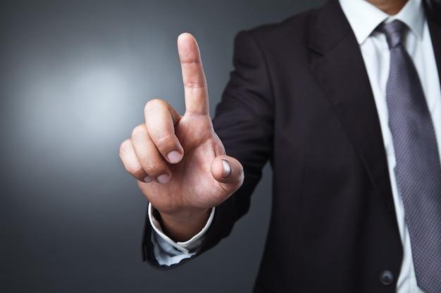 ボケ味の架空のボタンを押すビジネスマン