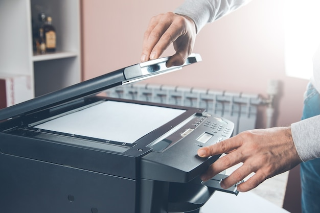 Businessman pressing button on the panel for using photocopier