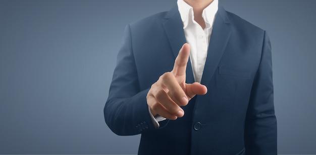 ボタン仮想画面を押すビジネスマン。未来的なインターフェースを指す手