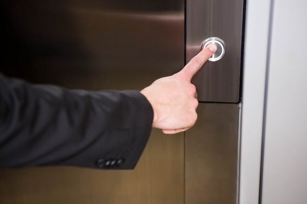 Businessman pressing elevator button in office