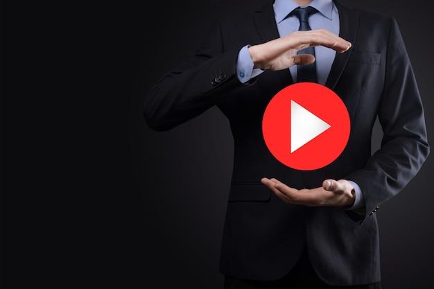 누르는 사업가, 프로젝트를 시작하거나 시작하기 위해 재생 버튼 기호를 누르고 있습니다. 비디오 재생 프리젠테이션. 비즈니스, technology.media 플레이어 버튼에 대한 아이디어입니다. 아이콘을 재생합니다. 이동합니다.