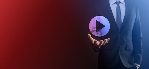Бизнесмен, нажав, удерживая кнопку воспроизведения, знак, чтобы начать или инициировать проекты. презентация воспроизведения видео. идея для бизнеса, технология. кнопка медиа-плеера. значок воспроизведения.