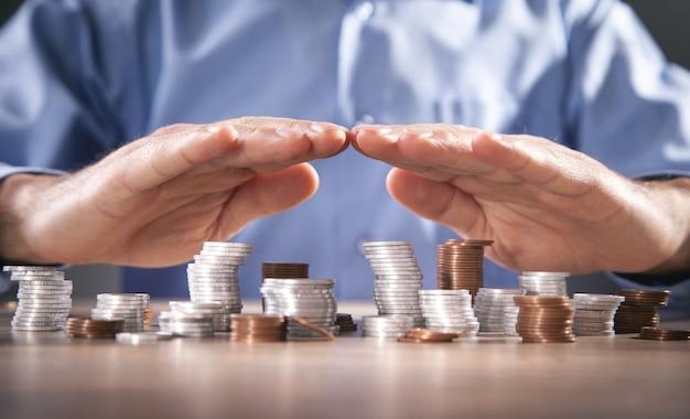 ビジネスマンはコインを保護します。お金を節約