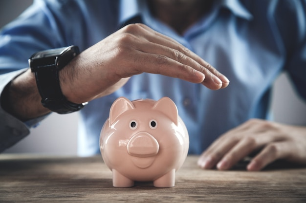 Businessman protect piggy bank. savings money concept