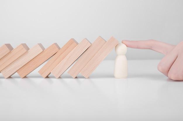 Бизнесмен защищает деревянный блок от падения планирования и стратегии в риске для бизнеса.