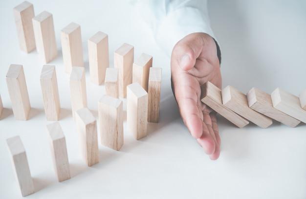 ビジネスマンは木製のブロックを保護します