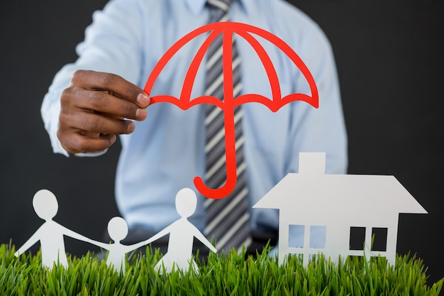 Businessman protecting paper cut out family, house and car with umbrella