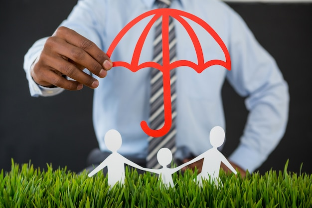 Businessman protecting paper cut out family with umbrella