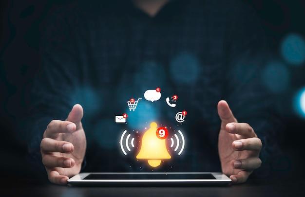 ビジネスマンは、仮想黄色のベルの呼び出し音とアプリケーション通知アラートの概念のアイコンでタブレットを保護します。