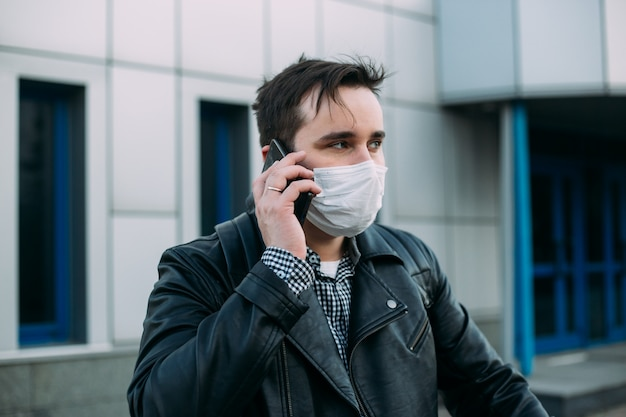 Businessman in protective mask using mobile phone