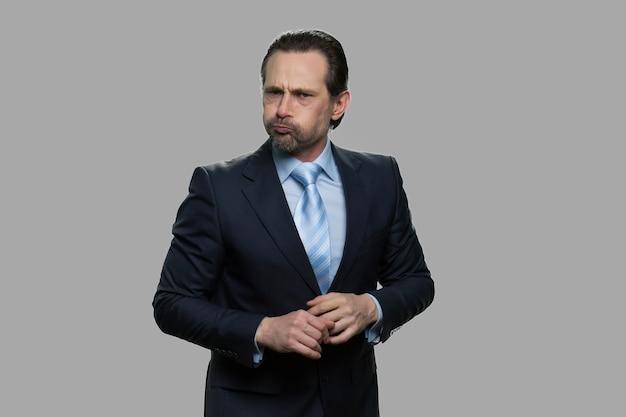 頬を膨らませるビジネスマン。変な表情のビジネスマン、空気で膨らんだ口。テキスト用のスペース。
