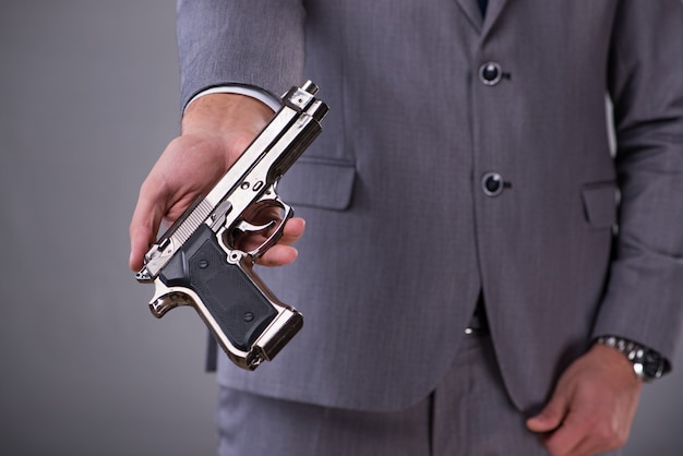 Businessman pulling the gun out of pocket