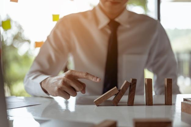 現代のオフィスで長い木製のブロックを引っ張ったり配置したりするビジネスマンは影響を示します