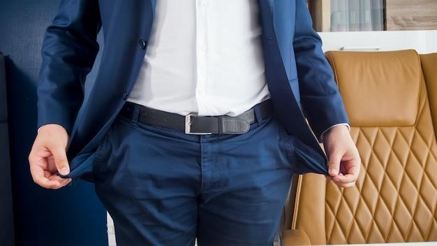 Бизнесмен, вытаскивая пустые карманы