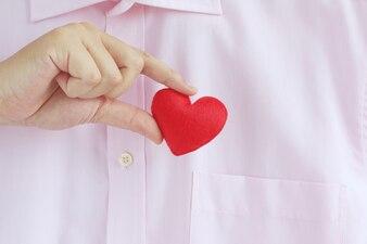 Бизнесмен вытаскивает или в красное сердце из кармана розовой рубашки