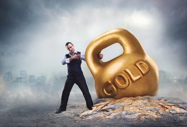 Бизнесмен тянет большую золотую гирю