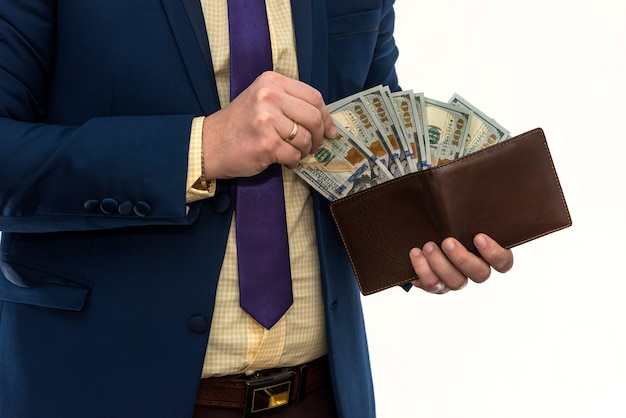 Businessman pulls out 100 dollar bill from his wallet to make a purchase or rent, isolated on white. man hold us money