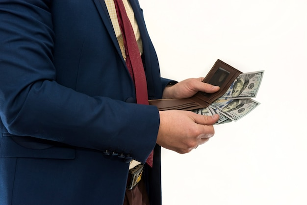 Businessman pulls out 100 dollar bill from his wallet to make a purchase or rent
