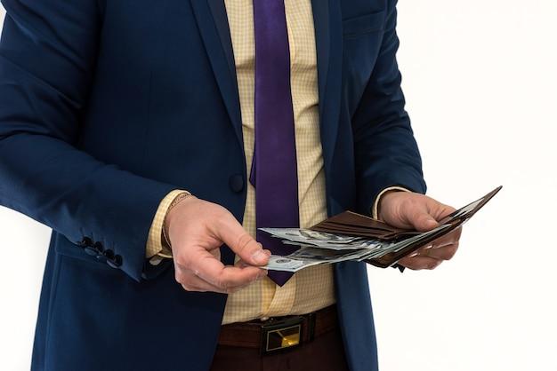 ビジネスマンは、白で隔離された購入または賃貸を行うために、財布から100ドル札を引き出します。男は私たちにお金を持っています