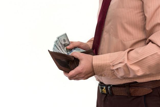 Бизнесмен вытаскивает 100-долларовую купюру из своего бумажника, чтобы сделать покупку или аренду, изолированные на белом. человек держит нам деньги