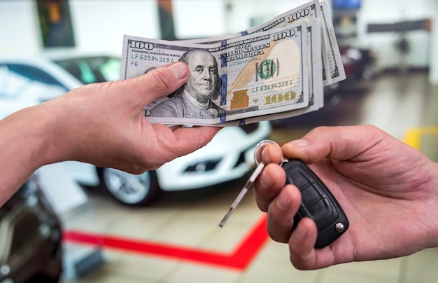 ビジネスマンはショールームで新しい車を購入し、ドルのお金を与え、車から鍵を取り、金融の概念