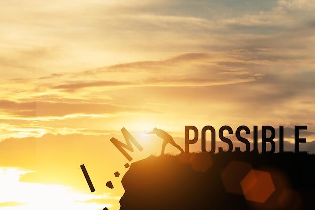 사업가 햇빛 산 꼭대기에 가능한 문구에 불가능한 문구를 밀어. 긍정적 인 사고 개념.