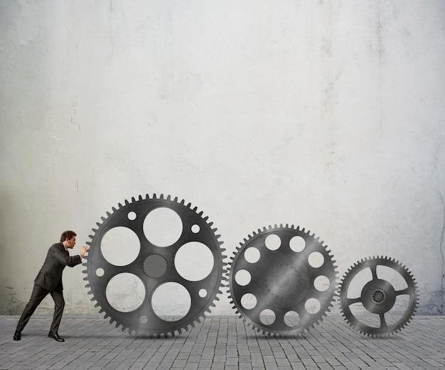 ビジネスマンは歯車のシステムメカニズムをプッシュします