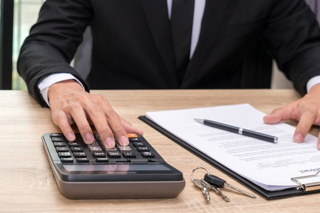 Businessman pushing calculator on wooden desk - buy home concept.