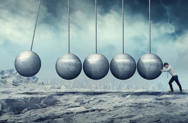 A businessman pushing at a hanging unmoving wrecking ball.