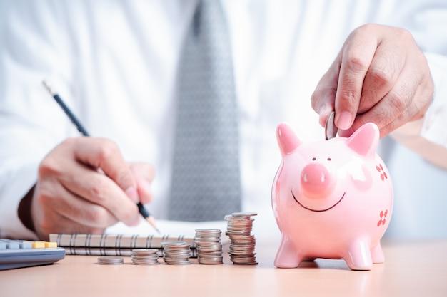 Businessman put coin to pink piggy bank,
