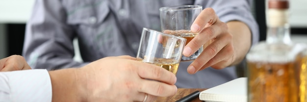 ビジネスマンは書類を置いてアルコールを飲む