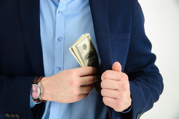 Businessman put money in his suit pocket