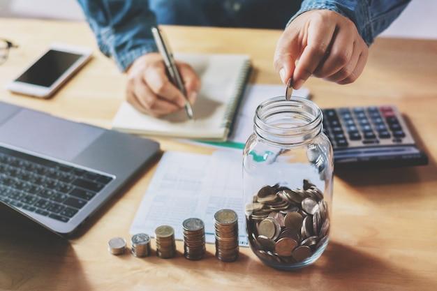 Businessman puting coins into jug glass