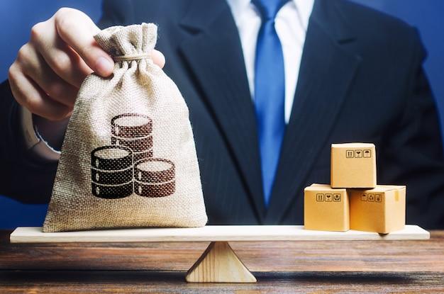 Бизнесмен ставит на весы мешок с деньгами и кучу коробок.
