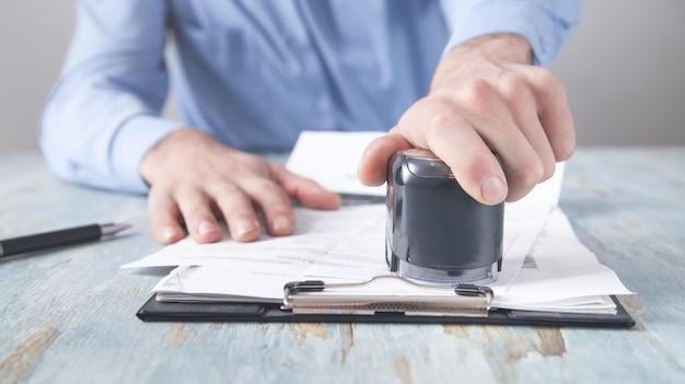 Бизнесмен ставит штамп на документах в офисе.
